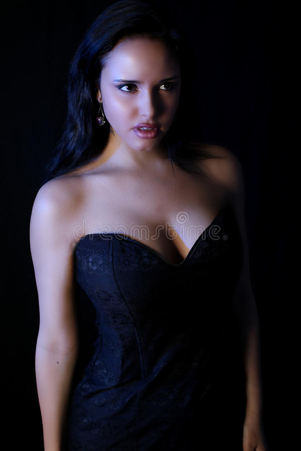 Beautiful vampire woman wearing a black dress stock images