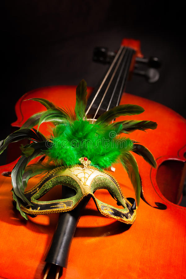 Beautiful Venetian mask with feathers on cello. Beautiful Venetian mask with green feathers on violoncello with the black background stock photo