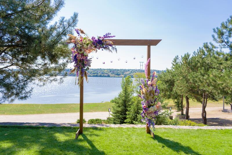 A beautiful venue for an open-air wedding ceremony. Wedding arch and rows of guest chairs on a green lawn overlooking the river stock photography
