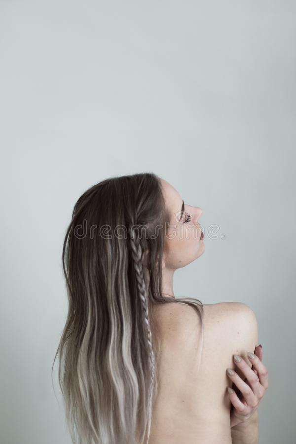 Beautiful vertical shot of a partially naked female model with braided highlighted hair. A beautiful vertical shot of a partially naked female model with braided stock image