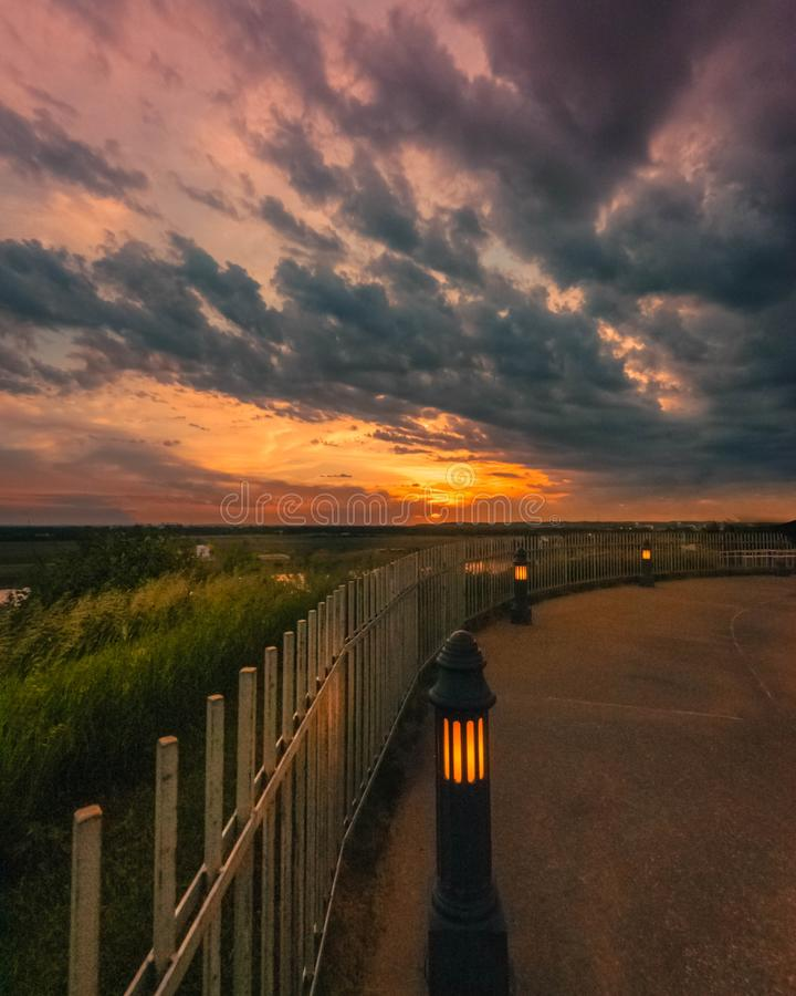Beautiful vertical shot of turned-on lamp posts near a fence under a cloudy sky during sunset. A beautiful vertical shot of turned-on lamp posts near a fence stock photos