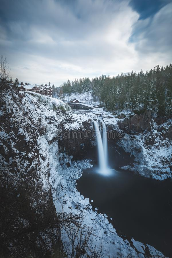 Beautiful vertical shot of waterfalls on glacier mountain near trees in Winter. A beautiful vertical shot of waterfalls on glacier mountain near trees in Winter royalty free stock photography