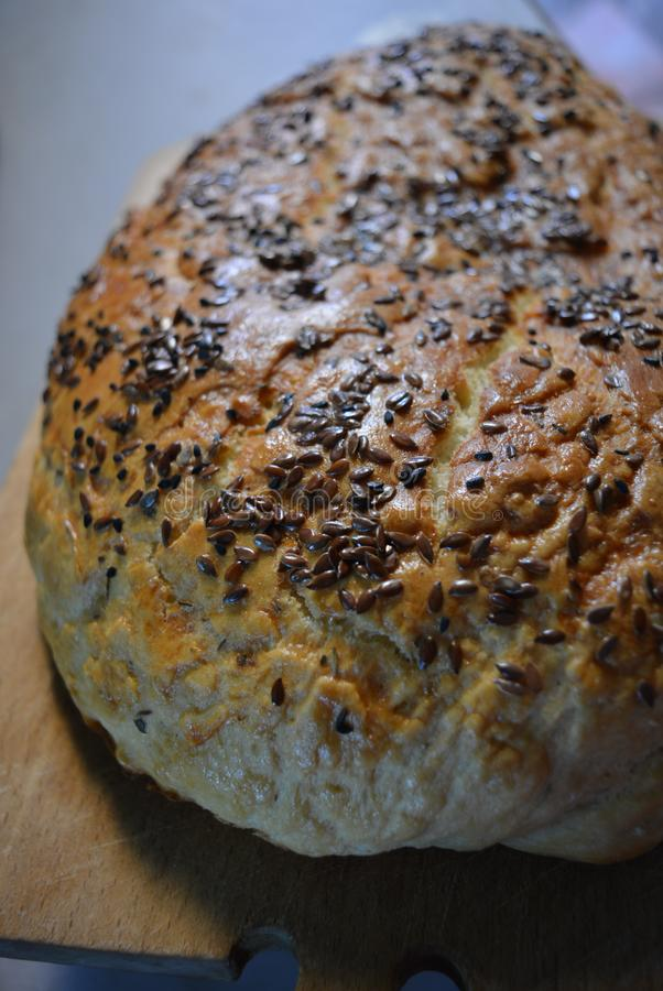 Beautiful very hearty bread homemade recipe. Brown bread with crispy crust, black caraway seeds and brown flax kernels. royalty free stock photography