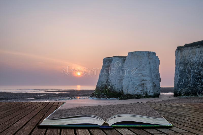 Beautiful vibrant sunrise over rock stacks on beach at low tide coming out of pages of open story book. Beautiful colorful sunrise over rock stacks on beach at stock photography