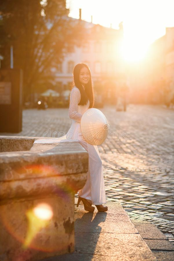 Beautiful Vietnamese girl dressed in traditional white Ao Dai dress stands near the fountain at the background of. Beautiful Vietnamese girl dressed in national royalty free stock photos