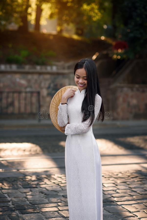 Beautiful vietnamese girl dressed traditional Ao Dai white dress. Ray of light on the background. stock images
