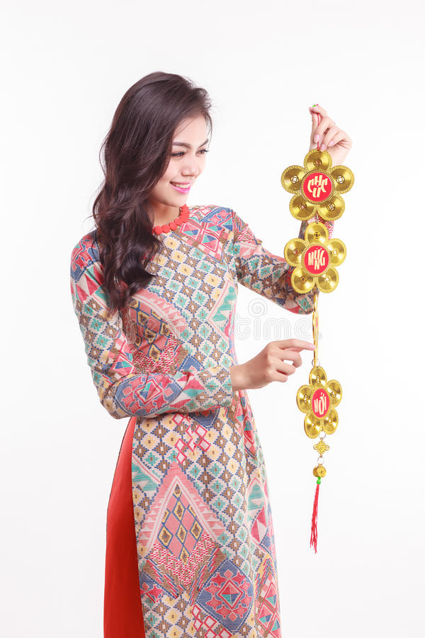 Beautiful Vietnamese woman wearing impression ao dai holding lucky decorate object. For celebrate lunar new year on white background royalty free stock images