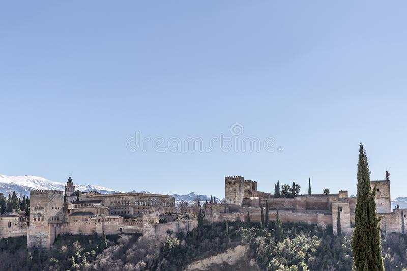 Beautiful view of the Alhambra on a hill with arid terrain with a snowy mountain in the background. A wonderful sunny day with a blue sky in Granada Spain stock image