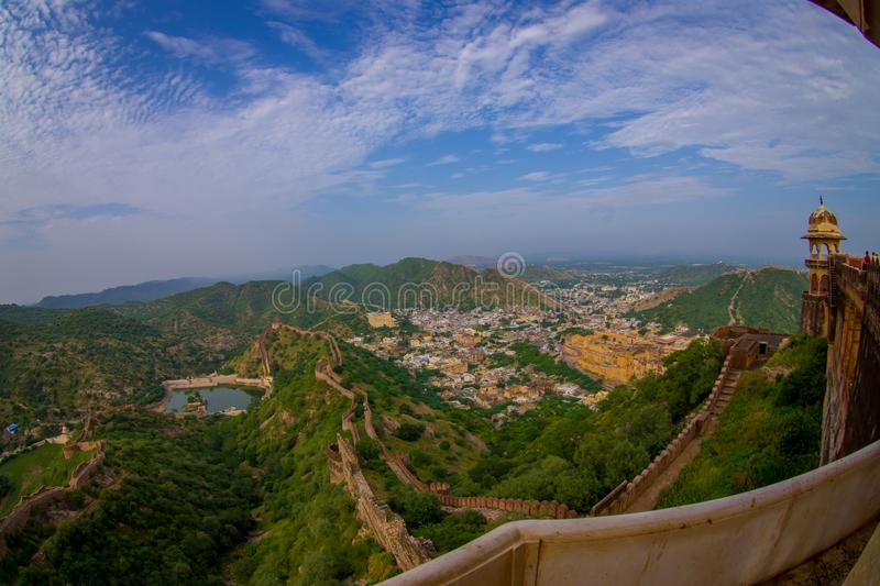 Beautiful view of the Amber fort in Rajasthan in Jaipur India with a stoned walls protecting the ancient indian palace. With some building houses in the royalty free stock photography