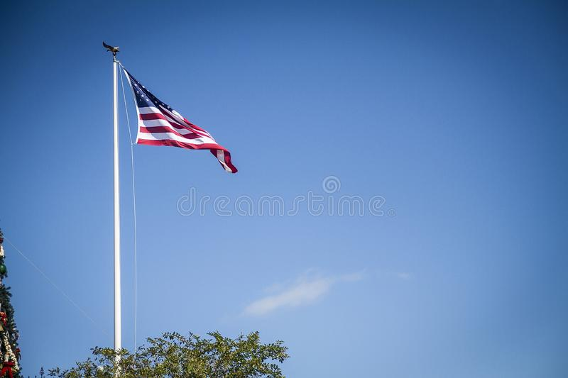 Beautiful view of the American Flag waving in the wind with the clear blue sky in the background royalty free stock images
