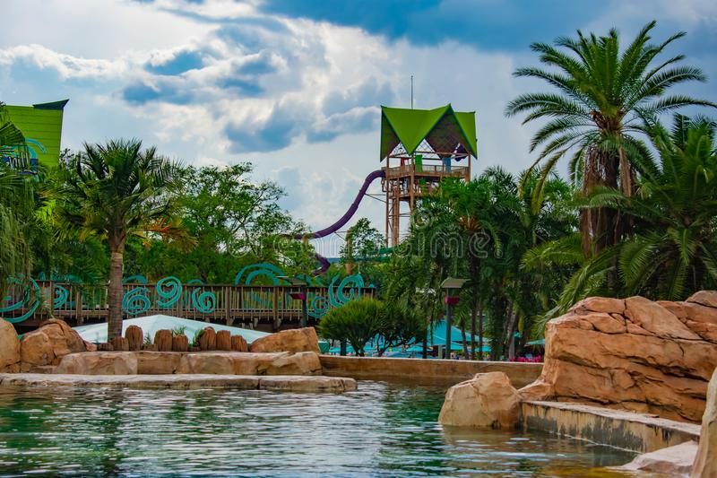 Beautiful view of Aquatica Tower, slide , palm trees and pool on cloudy sky background in International Drive area . Orlando, Florida. April 7, 2019. Beautiful royalty free stock photo