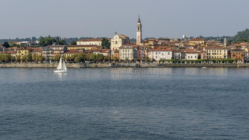 Beautiful view of Arona, Novara, Italy, with a sailboat sailing on Lake Maggiore. Beautiful view of Arona, Novara, Italy, Europe, with a sailboat sailing on Lake royalty free stock photography