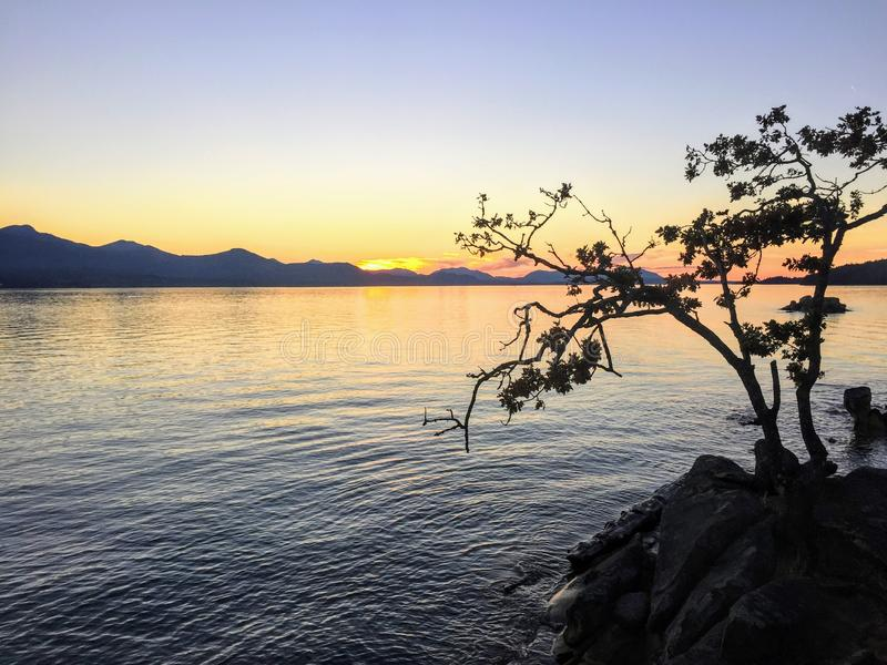 A beautiful view as the sun sets over the Cowichan Valley on Vancouver Island, British Columbia, Canada. The purple orange sunset is seen from Tent Island and stock photography