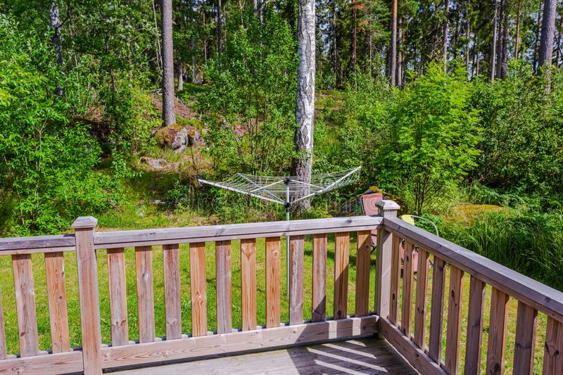 Beautiful view of backyard of private house with old wooden patio and  collapsible outdoor clothes dryer view. stock photo