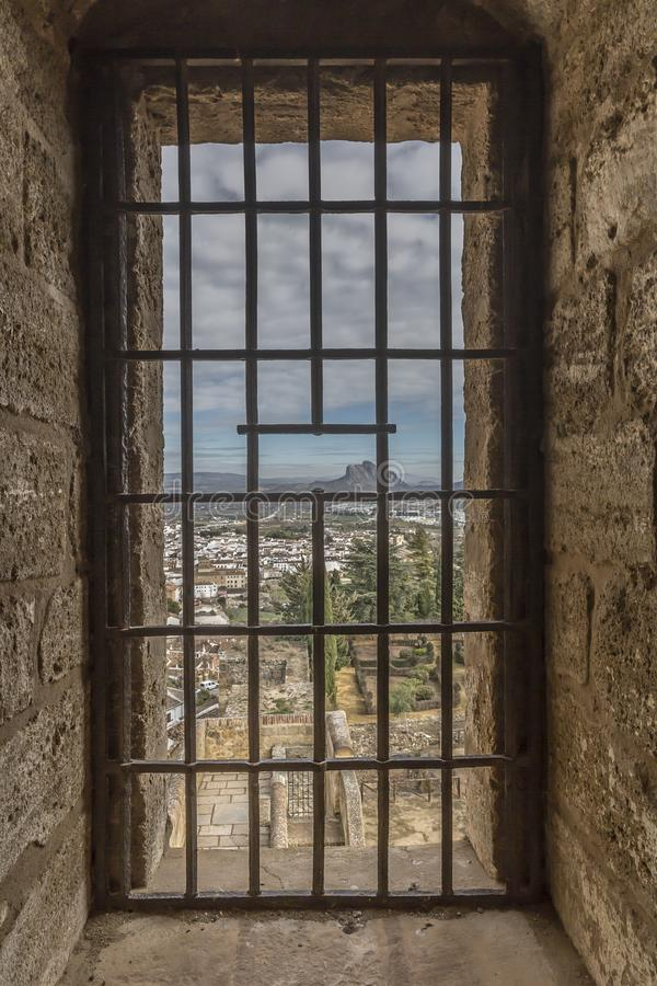 Beautiful view of the city and the Peña de los Enamorados or The Lovers` Rock through a window with metal grating. In the Alcazaba de Antequera, wonderful royalty free stock photo