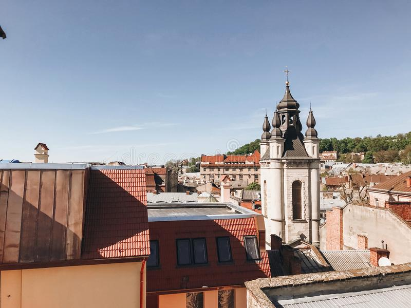 Beautiful view on city roofs and old cathedral on sunny day. Old city Lviv, cityscape of buildings and blue sky. Travel in Europe royalty free stock photography
