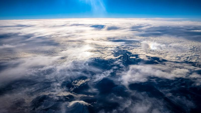 Beautiful view of the clouds and mountain under a clear sky shot from an airplane stock image