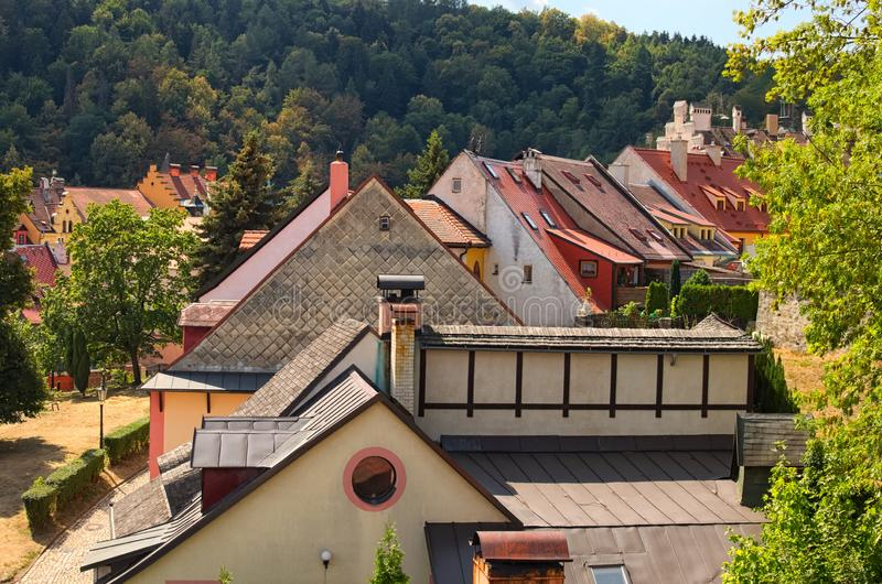 Beautiful view of colorful tile roofs of old residential houses with the trees in the forest at the background. Summer day. Loket, Bohemia, Sokolov stock image