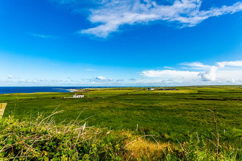 Beautiful view of a countryside with green grass, the sea in the background in the village of Doolin royalty free stock images