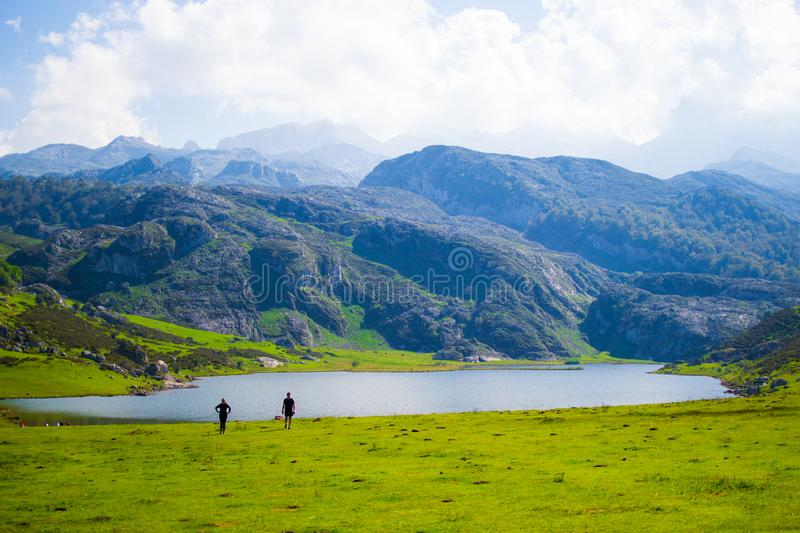 Beautiful view of Ercina Lake in Covadonga Lakes, Asturias, Spain. Green grassland with a couple walking and mountains at the. Background stock photos