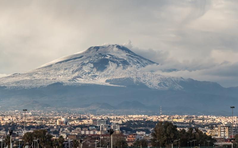 A beautiful view of the eruption of volcano Etna with smoke and snow and Catania city is in the photo in winter in Sicily. A beautiful view of the eruption of royalty free stock images