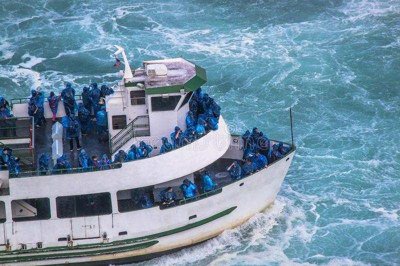 Beautiful view of excursion boat full with tourists in blue clothes. Tourist concept. Transportation concept.Niagara falls. stock photo