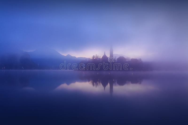Beautiful view of famous Bled Island with Catholic Church at scenic Lake Bled with Bled Castle Blejski grad and Julian Alps royalty free stock image