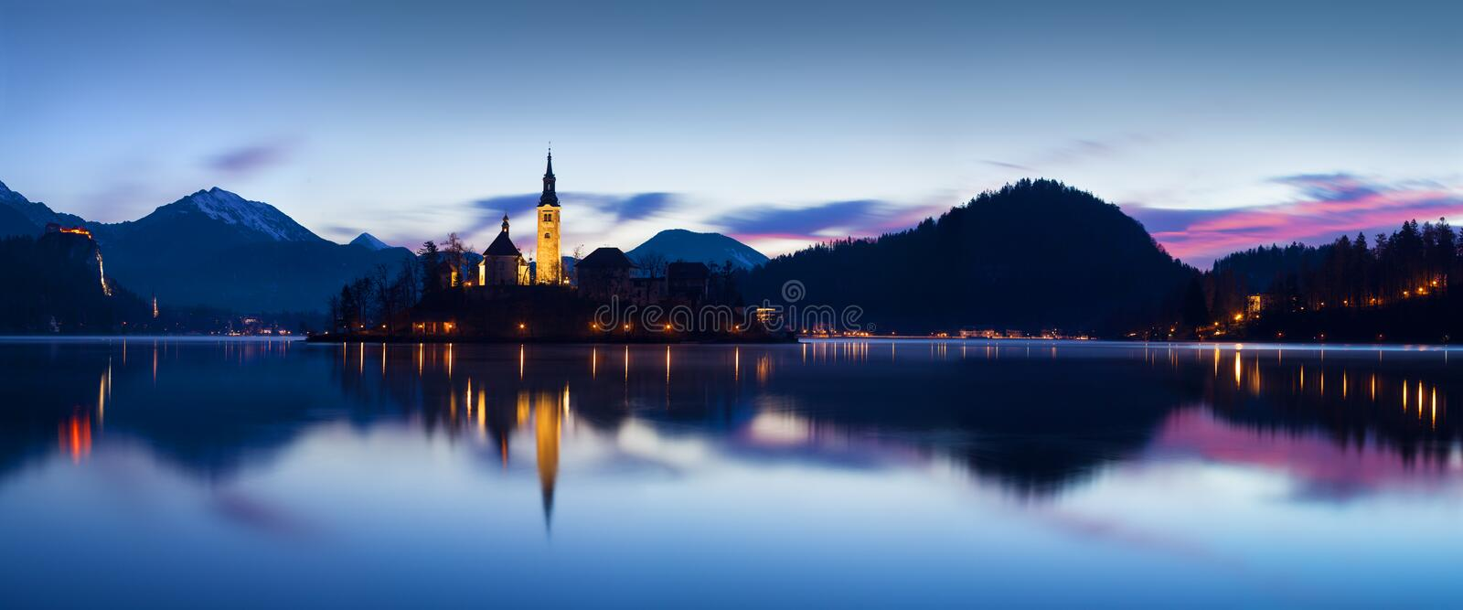 Beautiful view of famous Bled Island with Catholic Church at scenic Lake Bled with Bled Castle Blejski grad and Julian Alps. stock photo
