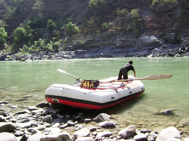Flowing River, Boat with Man and Mountain royalty free stock images