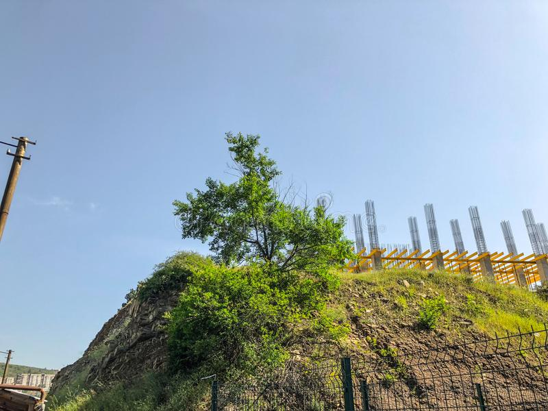 A beautiful view of the hillock with green grass against the sky, construction of a new building, a house frame, fittings.  royalty free stock photo