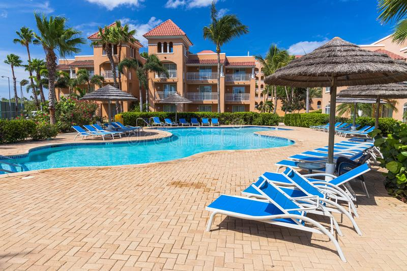 Beautiful view of hotel area. Outdoor pool with blue sun beds and umbrellas on green palm trees background.  Eagle Beach. royalty free stock photos