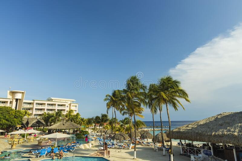 Beautiful view of hotel area. Outdoor pool with blue sun beds and umbrellas on green palm trees background. Willemstad. Curacao royalty free stock photo