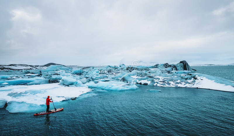 Beautiful view of icebergs glacier lagoon with a guy paddle boarding sup royalty free stock photography