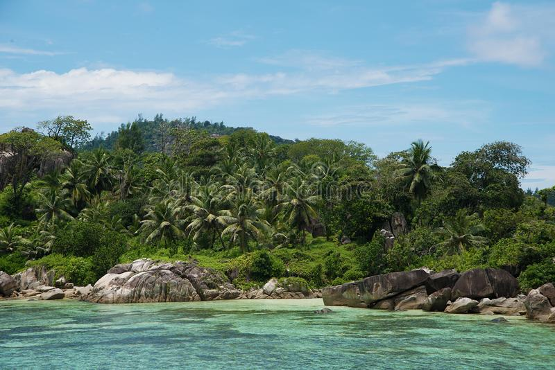 Beautiful view of the Indian Ocean from the island of Mae, Seychelles. On the ocean lie huge stones. Evergreen vegetation is in. The foreground stock photo