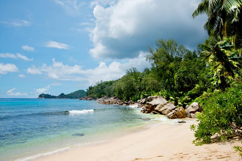 Beautiful view of the Indian Ocean from the island of Mae, Seychelles. On the ocean lie huge stones. Evergreen vegetation is in. The foreground stock photos