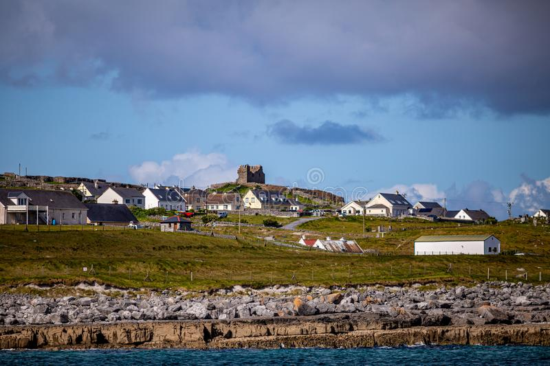 Beautiful view of the Inis Oirr island with its houses and the ruined castle tower in the background. Beautiful view of the Inis Oirr island with its houses and royalty free stock image