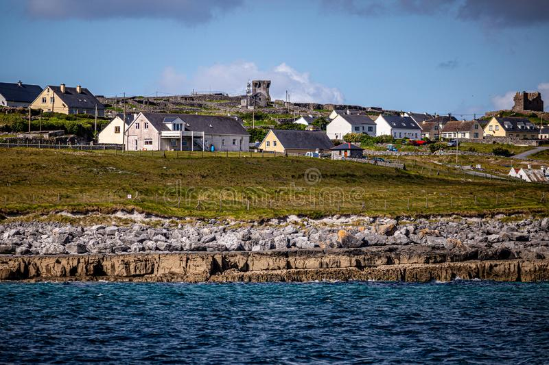 Beautiful view of the Inis Oirr island seen from a boat with its houses and the ruined castle tower in the background. Beautiful view of the Inis Oirr island royalty free stock photo