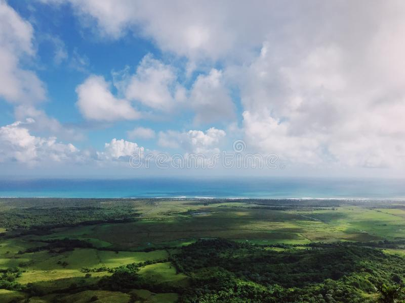 Beautiful view on the Lagoon Redonda and Atlantic Ocean from Redonda mountain. Green hills, blue sky, huge white clouds, sunlight spots on the grass royalty free stock photos