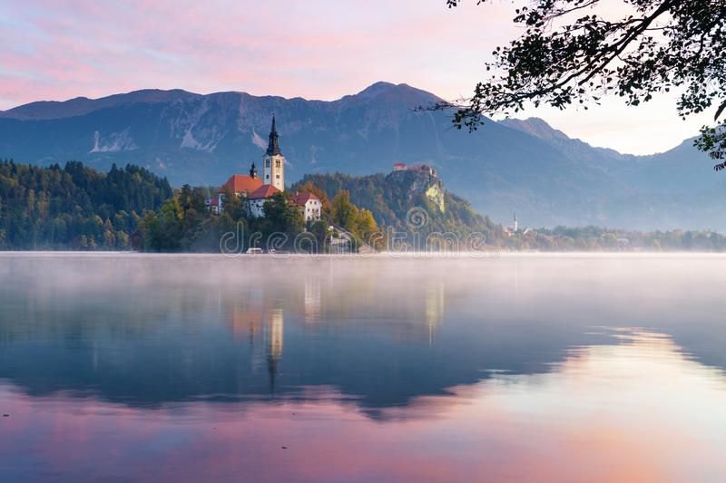 Sunrise at lake Bled. Church on island with castle and mountains in background. Beautiful view of lake Bled during sunrise in autumn. Fog lingering over the lake stock photo