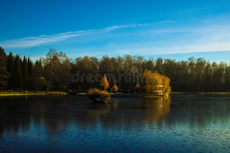 Beautiful view of the lake and the forest, reflected in the water, against the blue sky stock photos