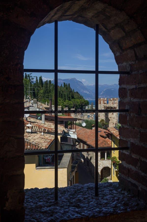 Beautiful view on Lake Garda (Italy), Sirmione and Italian Alps. Beautiful view on Lake Garda (Italy), Sirmione & Italian Alps through ancient window from stock photo