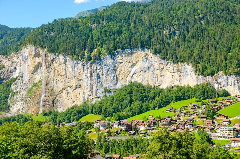 Beautiful view of Lauterbrunnen village in Switzerland with famous Staubach Falls on the rock above the small city. Alpine stock photo