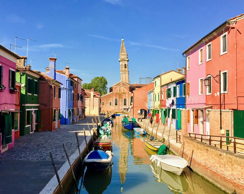 A beautiful view looking down a canal in Burano, Italy.  The houses are all different colours and the canal is full of boats. There is a historic church in royalty free stock photo