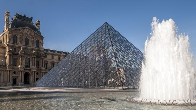 Beautiful view of the Louvre pyramid with fountain and water jets in action, Paris, France stock photo