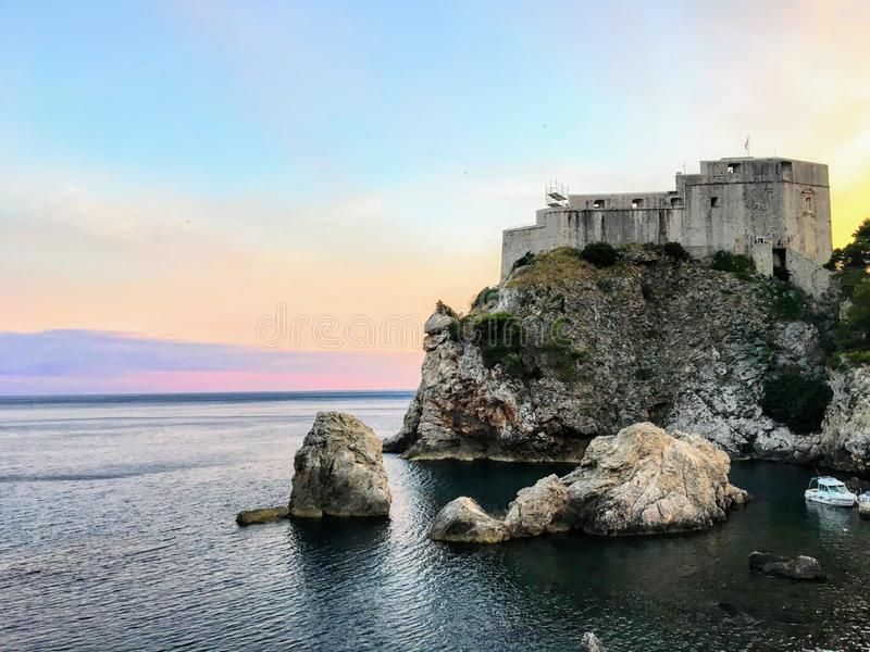 A beautiful view of the Lovrijenac tower, black water bay, and the adriatic sea in Dubrovnik, Croatia during sundown. royalty free stock photo