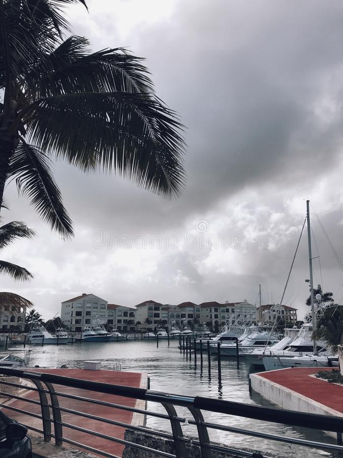 Beautiful view at marina of Cap Cana with luxury yachts and nice houses. Palms under cloudy sky. Weather is stormy. Sidewalks are red and facades are white stock photo