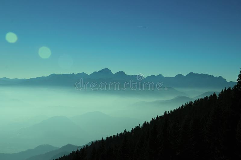 Beautiful view of the morning fog. Filling the valleys of smooth hills, blue morning fog, silhouette forest royalty free stock image