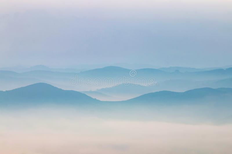Misty hills in the morning. Beautiful view of the morning fog filling the valleys of smooth hills royalty free stock photo