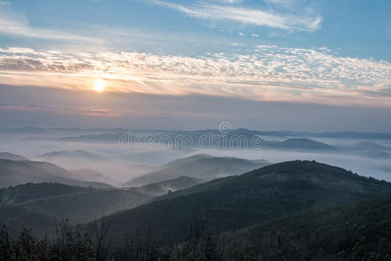 Misty hills in the morning. Beautiful view of the morning fog filling the valleys of smooth hills stock image