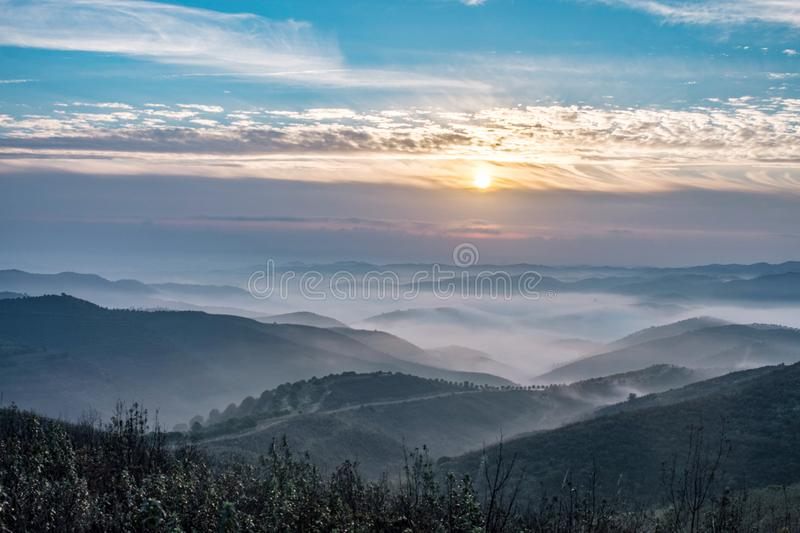 Misty hills in the morning. Beautiful view of the morning fog filling the valleys of smooth hills stock images